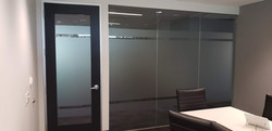 An office where the glass covering is a decorative stripe design that looks sleek and modern and sui