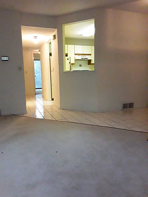 Empty dining area with tiled flooring and opening in wall to kitchen