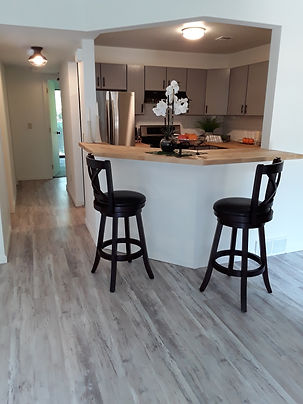Seating area with view into kitchen and hallway