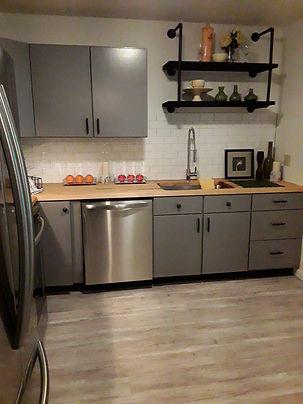 Custom shelving in brightly lit renovated kitchen