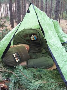 Instruktor testuje schronienie wykonane przez kursanta.