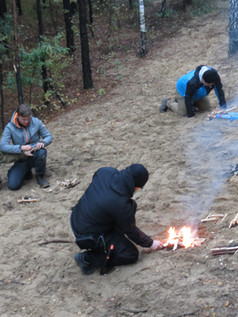Kursanci w trakcie rozpalania ognia krzesiwem.
