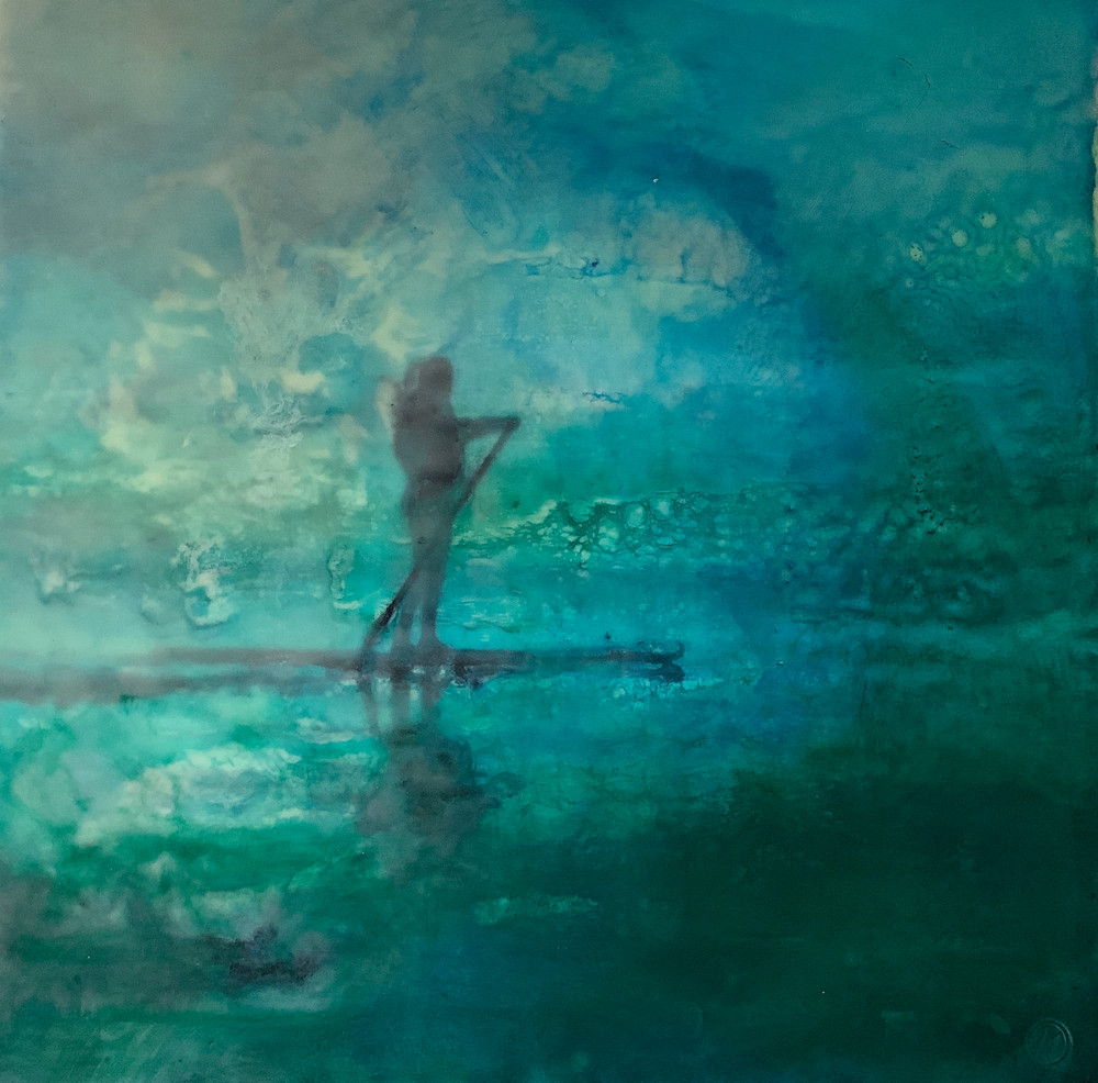 An encaustic image of a young woman on the sea on a stand up paddle board
