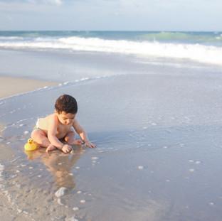 baby brincando na praia
