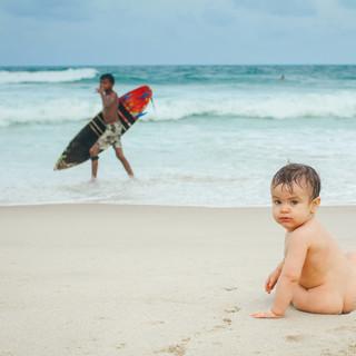 baby na praia com surfista