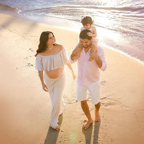 Gestante feliz com familia na beira do mar