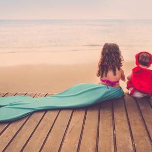 irmãs vestidas de ariel e sebastião na beira do mar