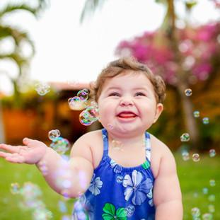 baby sorrindo feliz com bolhinhas de sabão