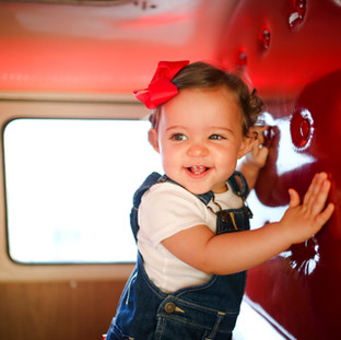 baby feliz dentro da kombi vermelha