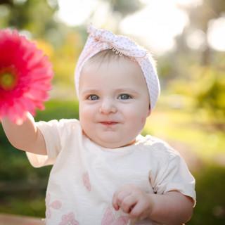 baby feliz segurando flor