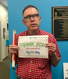 """A man in a plaid shirt wearing glasses holding a sign that says """"Thank you for supporting KY Gives Day"""
