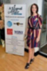 Tamara of KY Taste Buds and Radio Eye volunteer stands in front of sponsor sign
