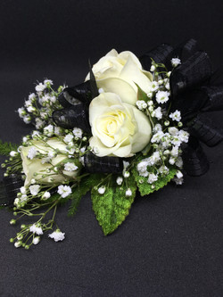 White roses and black ribbon corsage