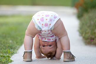 One-year baby girl playing upside down o