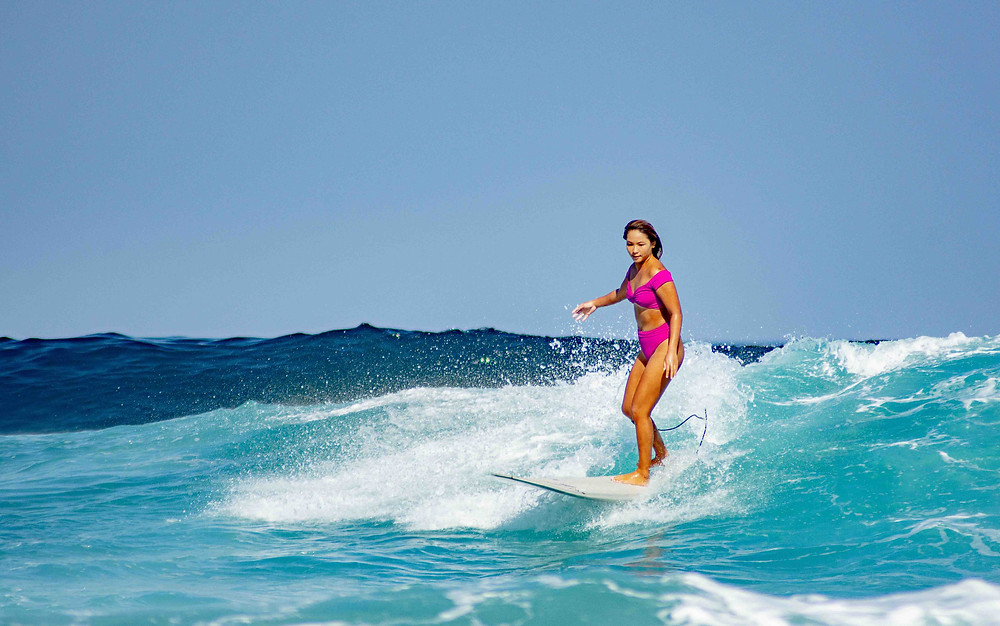 Beckie surfing in the Haikini Mona Liza Off-Shoulder set