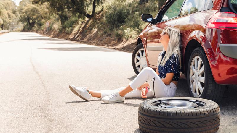 Mulher sentada ao lado do carro