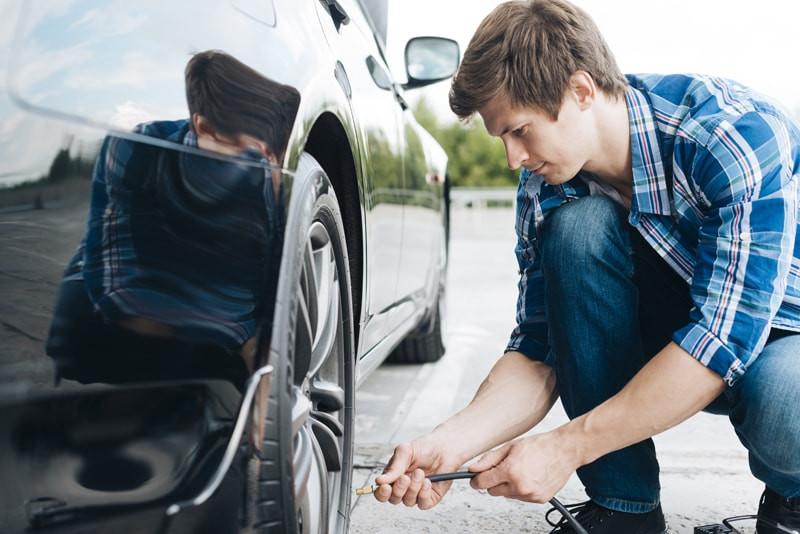 homem-calibrando-pneu-carro