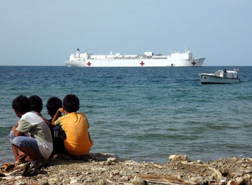 Young boys watch the USNS Mercy hospital ship sail past