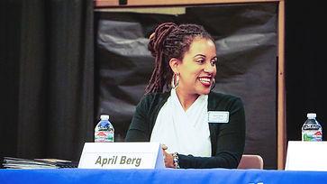 April Berg smiling at desk