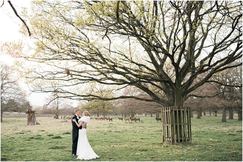 Bride at Groom kiss at Hampstead Heath overlooked by deer
