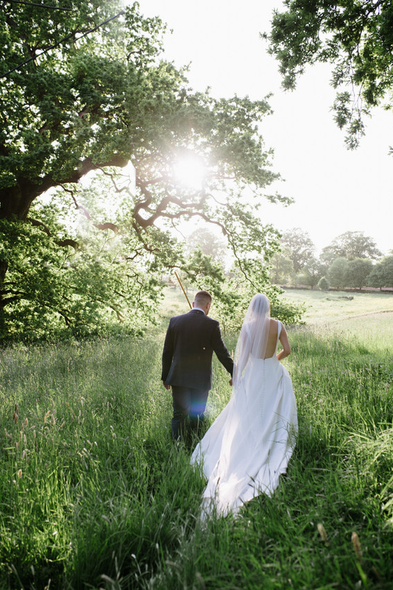 Bride and groom walk through the fields at sunset at Pennard house