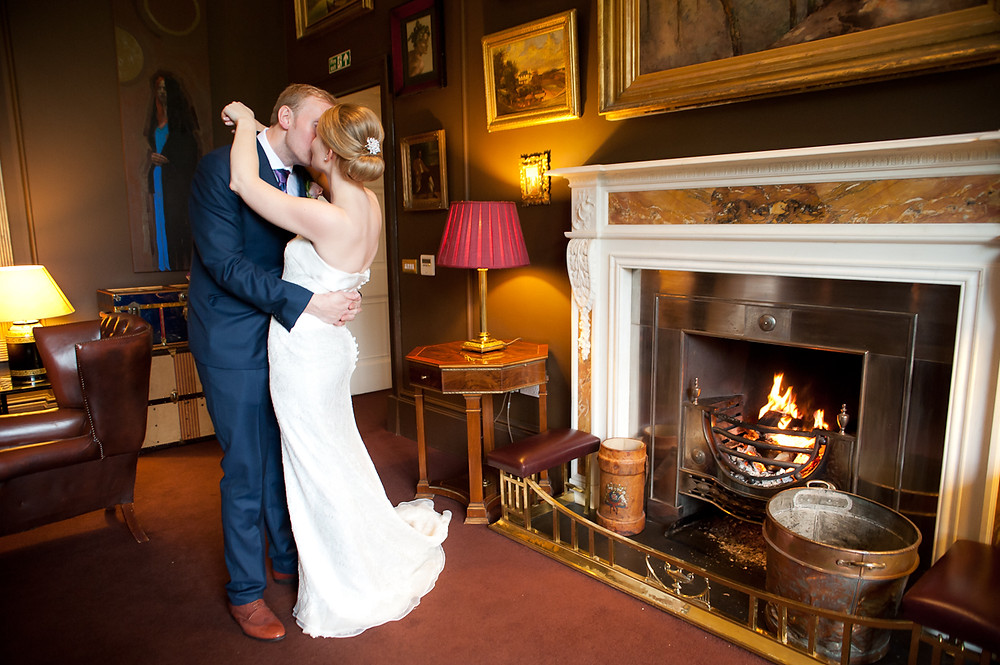 stubton hall wedding bride and groom in front of fire