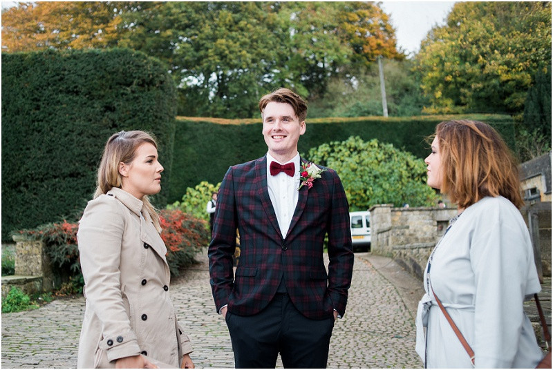 Groom in checked suit and red bowtie at Hilles House Cotswolds wedding venue