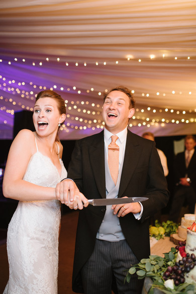 Bride and groom smile while cutting cake in marquee wedding