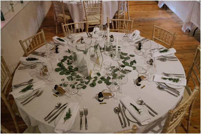 An elegant summer wedding at Pennard house in Somerset foliage filled reception room with gin favours