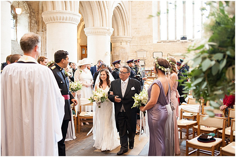 A military wedding at Malmesbury Abbey with a Charlie Brear dress and flower crowns