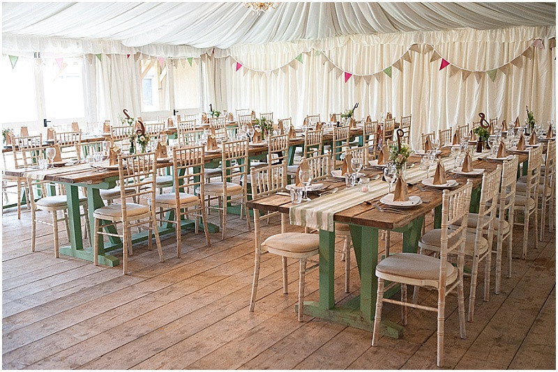 long wooden tables, chevalier chairs and bunting in marquee for wedding at The Moonraker Bradford-Upon-Avon