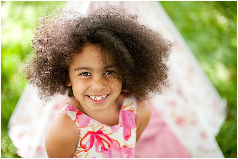 child smiling by a tippee for a childrens photo shoot in Gloucestershire