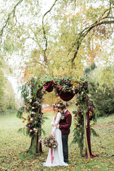 A boho bride and groom under a floral ceremony arch for boho wedding at Cotswolds wedding venue