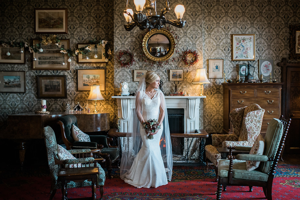 Bride with a stunning veil looks out of the window at Homme House