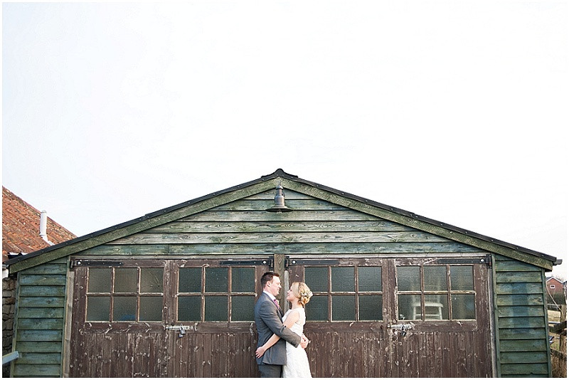 bride and groom in front of shed for winter wedding at The Moonraker