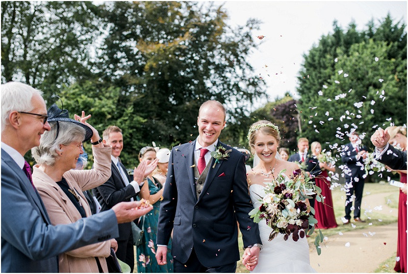 Cotswolds church wedding bride and groom confetti exit