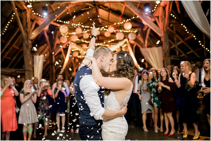 Bride and groom kiss under confetti during first dance by Cotswolds wedding photographer