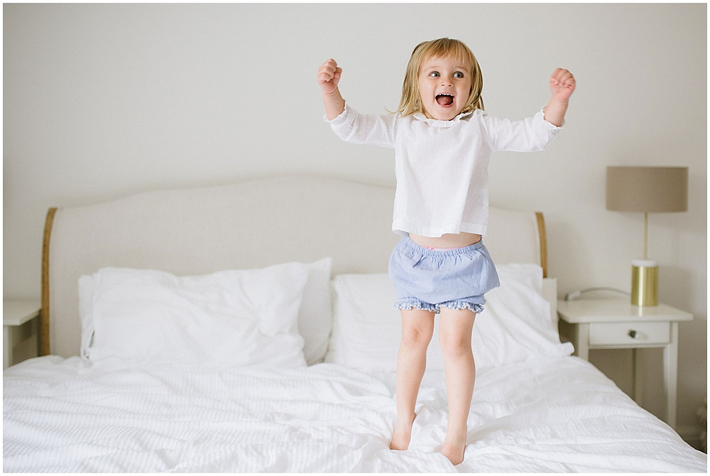 Cotswolds family photographer young girl jumps up and down on bed