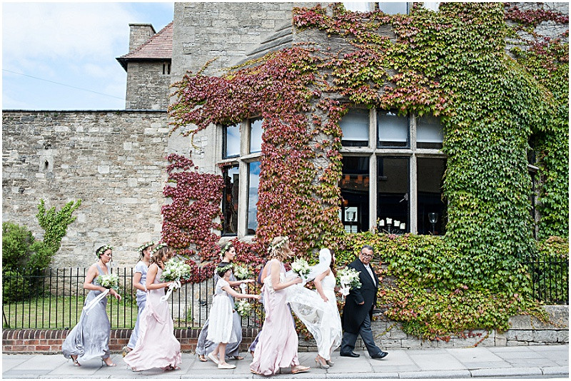 documentary wedding photography Malmesbury Abbey wedding with bridesmaids in mismatched pastel dresses from Ghost and a Charlie Brear wedding dress