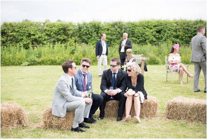 Boho tipi wedding Peak tipis Nottinghamshire guests sat on hay bales