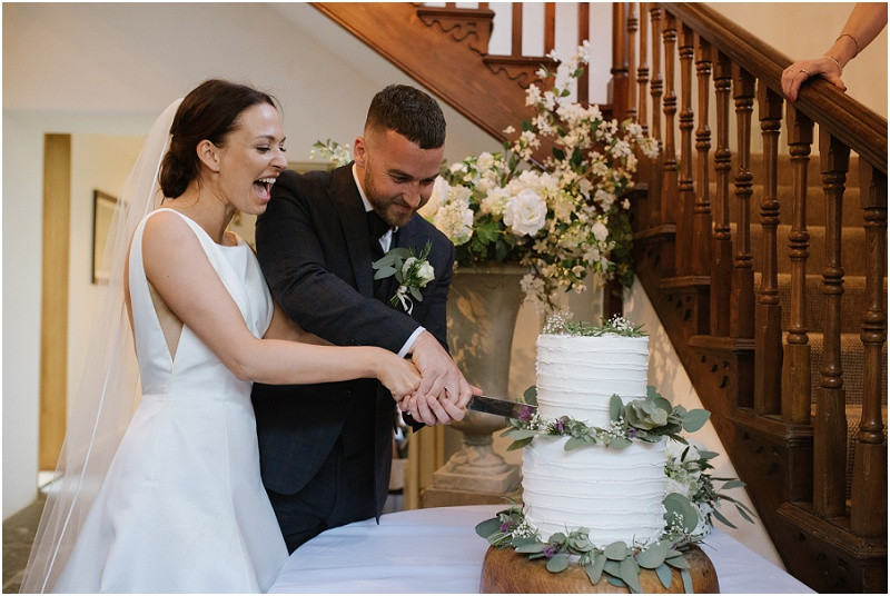 An elegant summer wedding at Pennard house in Somerset bride and groom cutting cake