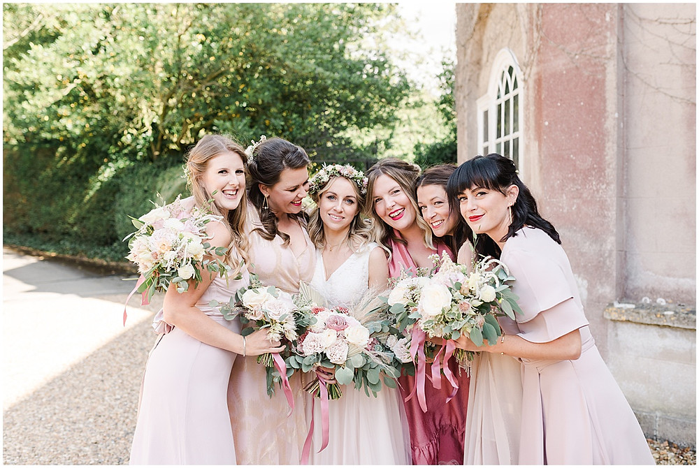 Get bridesmaid dress inspiration in this boho wedding from Pennard House wedding photographer with mismatched bridesmaid dresses in pink silk and flower crowns
