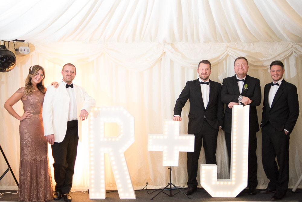 wedding party in tuxedo's and rose gold dress by illuminated light up letters