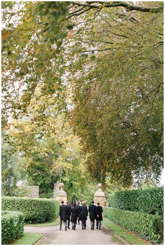 Grooms party walk along driveway at North Cadbury Court Wedding venue Somerset