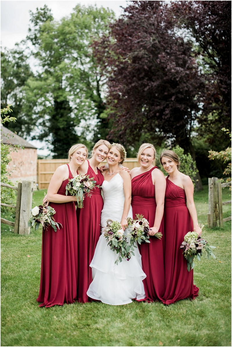 Bride in Essense of Australia and bridesmaids in red at Blackwell Grange Cotswolds wedding photographer