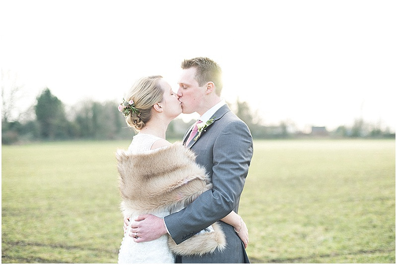 Bride and groom with stole and pink roses for winter wedding at The Moonraker