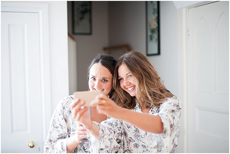 Bridesmaids taking a selfie in marching dressing gowns
