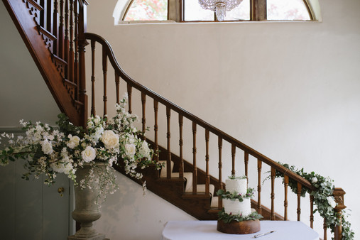 A staircase and cake full of flowers at Pennard house wedding venue somerset