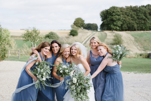 Bride and bridesmaids laughing at Cripps Stone Barn