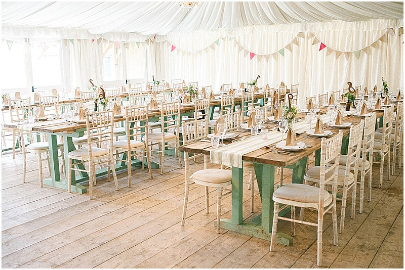 rustic marquee with wooden floors and long tables at The Moonraker